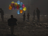 Afghan Boy Runs with Balloons to Join His Friends in Dusty Alley in Kabul, Afghanistan Impressão fotográfica