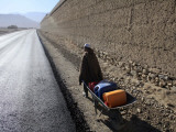 Child Uses a Wheel Barrow to Carry Jugs of Water, Logar Province, Afghanistan Photographic Print