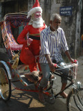 Indian Trishaw Driver Takes a Statue of Santa Claus to a Shop for Christmas Decoration in Agartala Photographic Print