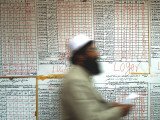 Electoral Worker Passes Election Results Posted on Wall at a Counting Center in Kabul, Afghanistan Photographic Print