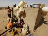 Refugee Children Wait their Turn to Collect Water Supplies at a Water Station in Sudan Fotografisk tryk