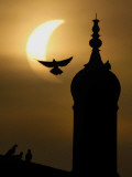 Partial Solar Eclipse Silhouettes Birds Surrounding a Minaret in Multan, Pakistan Photographic Print