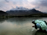 Afghan Man Washes His Face in the River before Going to Evening Prayers Photographic Print