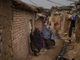Three Afghan Refugee Women and their Children Walk in an Alley of a Poor Neighborhood in Pakistan Photographic Print