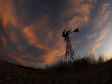 Old Windmill Silhouetted Against Clouds Colored by the Setting Sun Photographic Print
