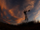 Old Windmill is Silhouetted Against Clouds Colored by the Setting Sun Photographic Print