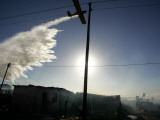 Aircraft Releases Water, Fighting a Fire in an Informal Settlement in Cape Town, South Africa Photographic Print