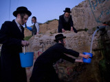 Ultra-Orthodox Jewish Men Stand Next to a Well as They Fill Canisters with Water in Jerusalem Photographic Print