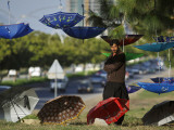 Pakistani Road Side Vendor Standing Next to His Display of Umbrellas for Sale Photographic Print