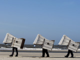 Workers Carry Beach Chairs Along the Beach of St. Peter-Ording at the North Sea, Northern Germany Photographic Print