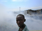 Youth Walks by Burning Garbage in Cite Soleil, Port-Au-Prince Photographic Print