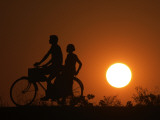 Returning to their Village after the Day's Work on a Bicycle as the Sun Sets Photographic Print