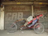 Indian Rickshaw Puller Rests in the Shade at a Closed Market Complex in New Delhi, India Photographic Print