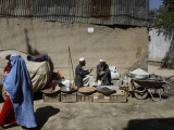 Afghan Street Vendor Speaks with Friend as He Sells Mulberry Pea Nuts and Sun Flower Seeds in Kabul Photographic Print