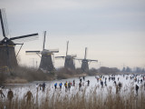 People Skate on Frozen Canals in Kinderdijk's Mill Area, a UNESCO World Heritage Site, Netherlands Papier Photo