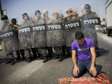 Palestinian Worshipper Prays Outside Jerusalem's Old City While Israeli Forces Stand Guard Photographic Print