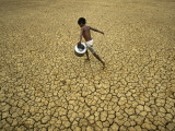Indian Village Boy Runs Through a Parched Field on World Water Day in Berhampur, India Photographic Print