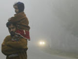 Indian Worker Carries His Daughter in the Morning Fog in the Outskirts of Jammu, India Photographic Print