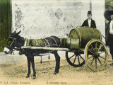 Two Caucasian Men in a Street Scene - a Small Donkey Pulls a Large Barrel on a Cart Photographic Print