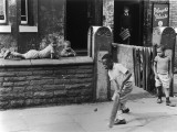 Young Black Boys Play Cricket on the Pavement in Manchester. Photograph by Shirley Baker Photographic Print by Shirley Baker