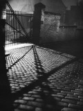 Spooky Shadow Patterns from an Iron Gate across a Cobbled Street .. Photographic Print