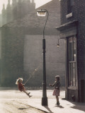 Two Girls Swing on a Lampost - Manchester 1965 Photographic Print by Shirley Baker