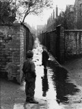 Two Boys Playing in a Large Puddle - Manchester, 1966 Photographic Print by Shirley Baker