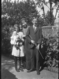 Three Children Photographed in the Garden - a Girl Holds a Doll Photographic Print by Vanessa Wagstaff