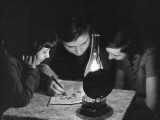 Three Children Do a Crossword by Lamp Light Photographic Print