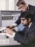 Two Technicians Check a Computer Printout Photographic Print by Heinz Zinram