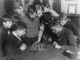 Two Boys Sit for a Game of Chess. Eight Spectators Look On Photographic Print