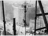 A Man Hangs Precariously from a Line During the Construction of a Skyscraper in New York Photographic Print