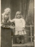 A Small Girl Poses with a Small White Dog Photographic Print