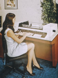 A Young Woman Office Worker Using What Now Looks Like a Rather Cumbersome Computer Photographic Print