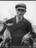 A Cotswolds Farmer Holds Two New-Born Lambs Photographic Print by Henry Grant