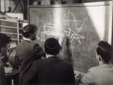 A Group of Scientists Study a Problem by Using Diagrams on a Blackboard Photographic Print by Henry Grant
