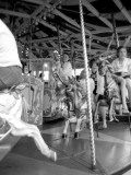 Children and Adults Ride a Carousel at a Funfair in Surrey Photographic Print by Vanessa Wagstaff
