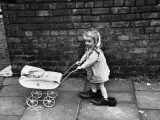 Little Girl with Toy Pram in Large Shoes - Manchester 1966 Photographic Print by Shirley Baker
