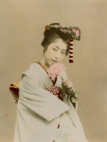 A Japanese Girl in Traditional Costume and Elaborate Hairstyle Smelling a Pink Flower Photographic Print