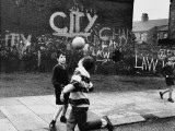 Boys Play Football in the Street - Moss Side, Manchester Photographic Print by Shirley Baker