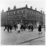 In Liverpool, a Lollipop Lady Helps Children Cross a Cobbled Street Photographic Print by Henry Grant