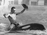 A Man with a Cowboy Hat Rides a Killer Whale Photographic Print