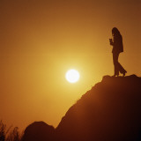 Silhouette of Woman on Hill at Sunset Photographic Print by Dennis Hallinan