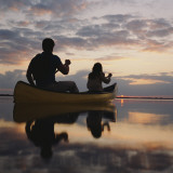 Couple Rowing Canoe in Lake at Sunset Photographic Print by Dennis Hallinan
