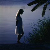 Silhouette of woman standing near a lake Photographic Print by Dennis Hallinan