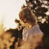 Woman Holding Flower Outdoors at Dusk Photographic Print by Dennis Hallinan