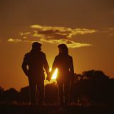 Couple Walking Holding Hands at Sunset Photographic Print by Dennis Hallinan