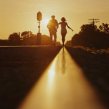 Silhouette of Couple Walking on Railroad Tracks at Sunset Photographic Print by Dennis Hallinan