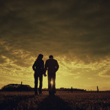 Couple Walking at Sunset Holding Hands Photographic Print by Dennis Hallinan