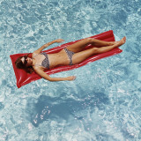 Woman Sunbathing in Swimming Pool Float Photographic Print by Dennis Hallinan